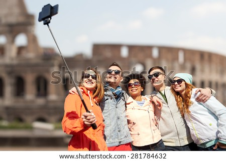 tourism, travel, people, leisure and technology concept - group of smiling teenage friends taking selfie with smartphone and monopod over coliseum ruins in rome background - stock photo