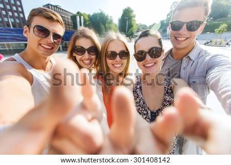 tourism, travel, people, leisure and technology concept - group of smiling teenage friends taking selfie and showing thumbs up outdoors - stock photo