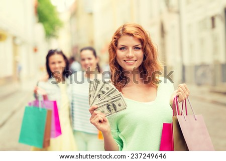 tourism, travel, vacation, shopping and friendship concept - smiling teenage girls with shopping bags on street - stock photo