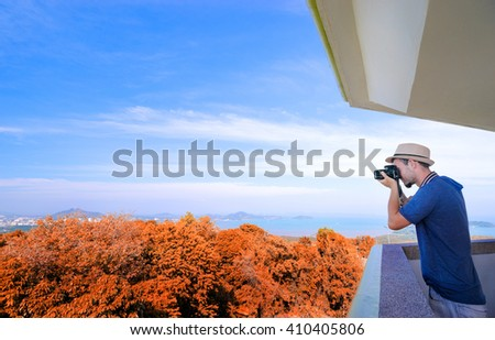 Tourist attraction. Traveler taking photo with camera on the view point enjoying sea, city and sky. - stock photo