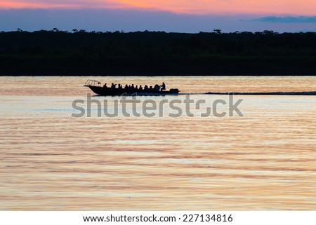 Tourist boat cross the Amazon river at the sunset. Iquitos, Peru - stock photo