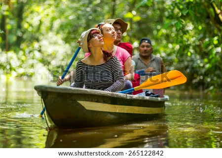 TOURIST BOAT NAVIGATING ON MURKY AMAZONIAN WATER IN CUYABENO WILDLIFE RESERVE  - stock photo