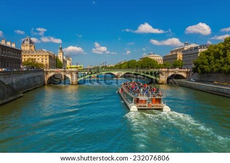 Tourist boat near Conciergerie and bridge Pont Notre-Dame over river Seine in Paris, France - stock photo