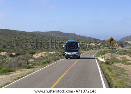 TOURIST BUS DRIVING ON HIGHWAY, BAJA, MEXICO - January 20, 2016: bus going fast on the desert mountain highway