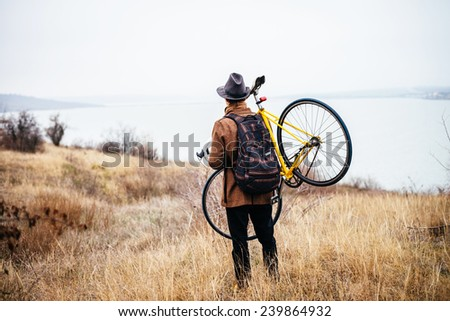 tourist carrying his broken bike on the forest road - stock photo