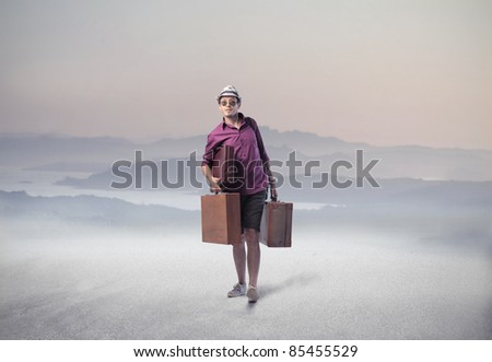 Tourist carrying some suitcases in a desert - stock photo