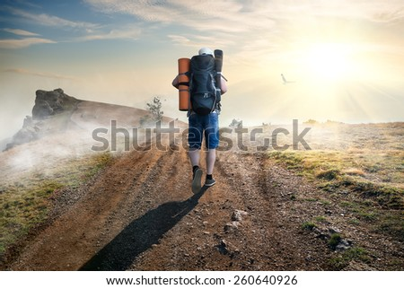 Tourist climbing to the mountains by the road - stock photo