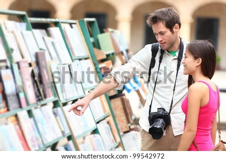 Tourist couple in Havana, Cuba looking at books together having fun on vacation travel on Plaza de Armas in Old Havana. Young travelers interracial couple, Asian woman, Caucasian man. - stock photo
