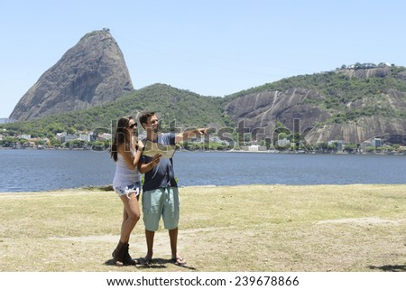 Tourist couple in Rio de Janeiro in front of the Sugar Loaf Mountain, Brazil  - stock photo