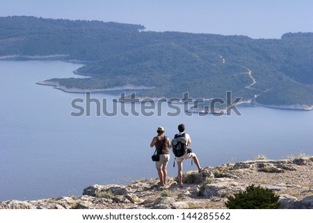 Tourist couple looking at Hvar island from Vidova Gora on island Brac