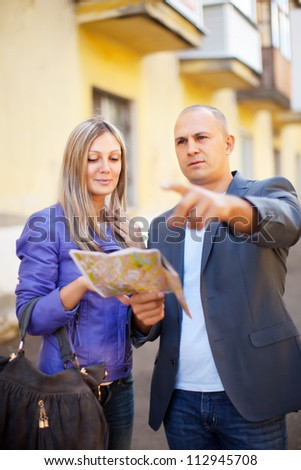 tourist couple looking at the map in the city