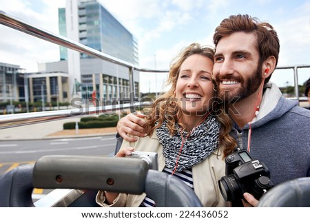 tourist couple on open top bus tour guide around the city in vacation