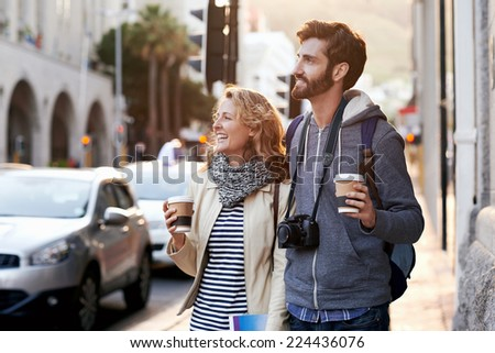 tourist couple travel with coffee ab camera walk through city having fun - stock photo