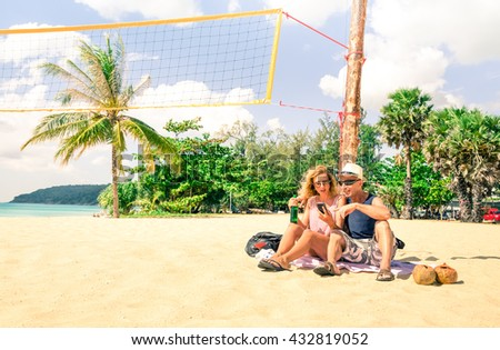 Tourist couple using mobile phone on the beach at Phuket Island - Travel friends looking holiday pictures sitting on the white sand - Concept of relax and technology in a tropical destination tour - stock photo