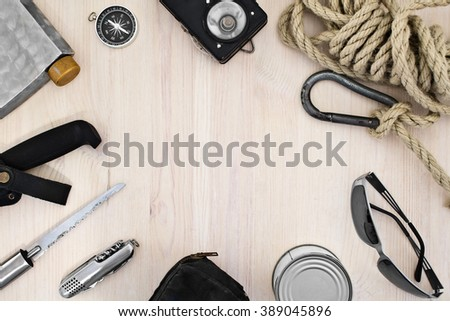 Tourist equipment. Set of items for recreation and tourism on a light wooden background. Retro composition with space for text.