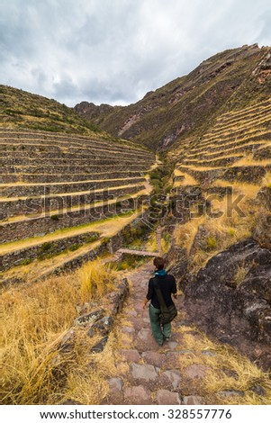 Tourist exploring the Inca Trails and the majestic terraces of Pisac, Sacred Valley, major travel destination in Cusco region, Peru. Vacations and adventures in South America. - stock photo