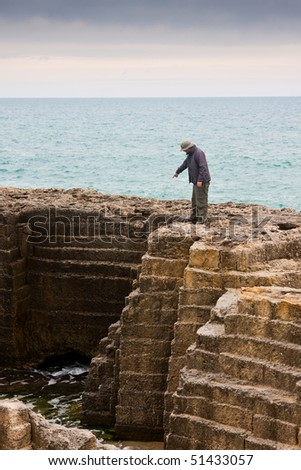 Tourist getting splashed at an ancient quarry by the sea at Torre Egnatia, close to Bari, in Italy. - stock photo