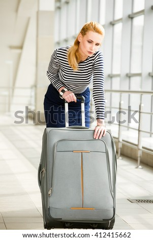 tourist girl blonde in a striped jacket pulling a large suitcase at the station. Attractive girl carries a suitcase. - stock photo