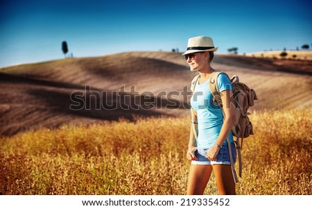 Tourist girl enjoying view of beautiful dry golden wheat hills, traveling along Europe in autumnal season, active lifestyle concept   - stock photo