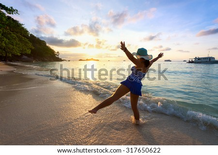 Tourist girl in a swimsuit blue and white striped hat standing on beach with pleasure the beautiful landscape of sky and sea during sunrise, Miang island, Similan National Park, Phang Nga, Thailand