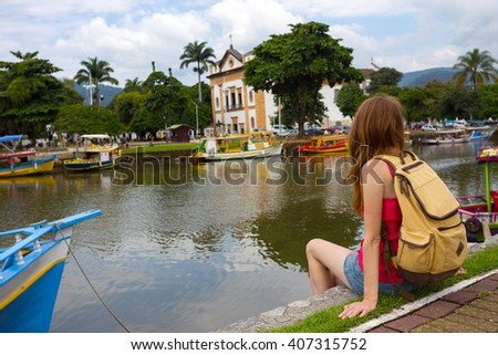 Tourist girl sitting on the dock with colorful boats in the bay of the famous historical town Paraty, Brazil
