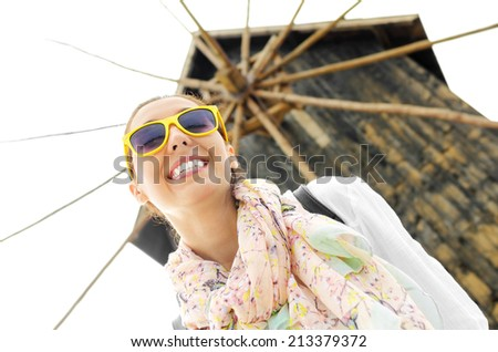 Tourist girl with a smile on his face and yellow glasses on the background of the old mill