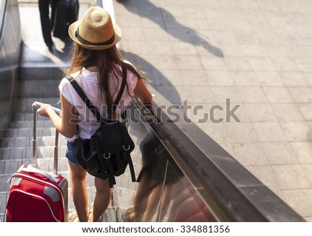 Tourist girl with suitcase down the escalator. - stock photo