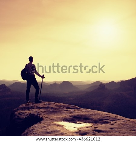 Tourist guide on cliff edge with pole in hand. Hiker with sporty backpack stand on rocky view point above misty valley. Sunny spring daybreak in rocky mountains.