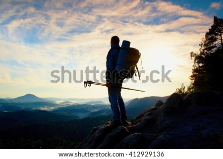 Tourist guide on the way with pole in hand. Hiker with sporty backpack stand on rocky view point above misty valley. Sunny spring daybreak in rocky mountains. - stock photo