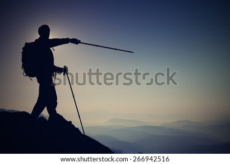 Tourist guide show right way with pole in hand. Hiker with sporty backpack stand on rocky view point above  misty valley. Sunny spring daybreak in rocky mountains. Mountain adventure guide. Man hike - stock photo
