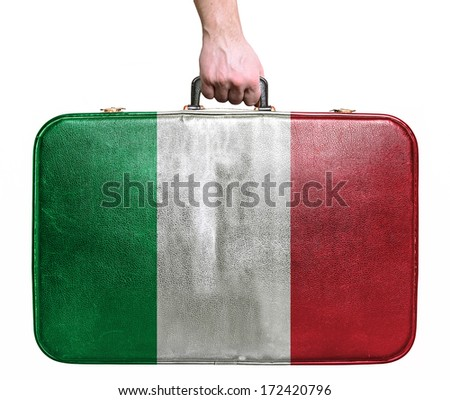 Tourist hand holding vintage leather travel bag with flag of Italy - stock photo