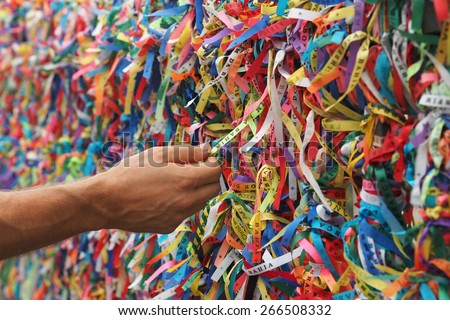 Tourist hand touching colorful Senhor do Bonfim ribbons at Pelourinho in Salvador, Bahia, Brazil. - stock photo