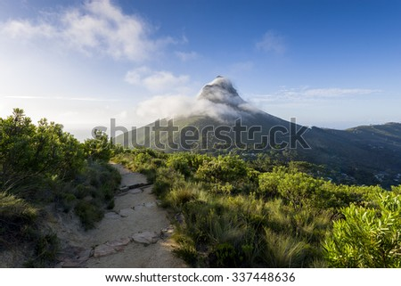 Tourist hikers up Cape Town, Table Mountain landscape, overlooking Lions Head peak
