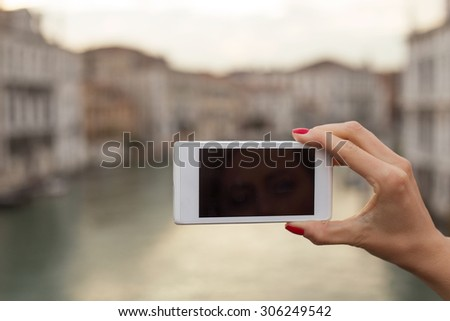 Tourist holding mobile phone - stock photo