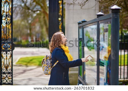 Tourist in London, looking at the information board with park map - stock photo