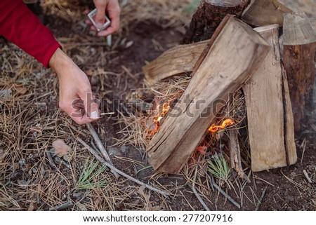 tourist in red sweater in a pine forest with a match ignites a fire of oak logs - stock photo
