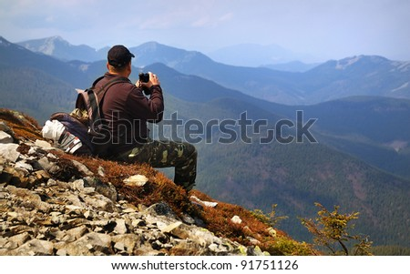 tourist in the mountains looking through binoculars