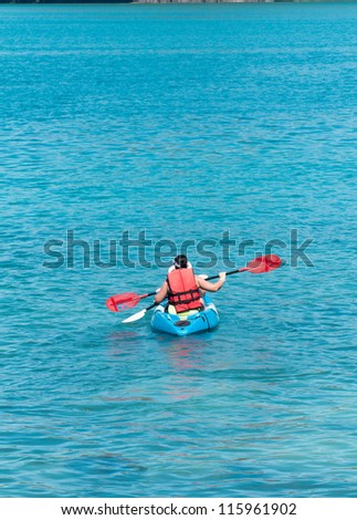 Tourist  kayaking in the Thai ocean from backward view - stock photo