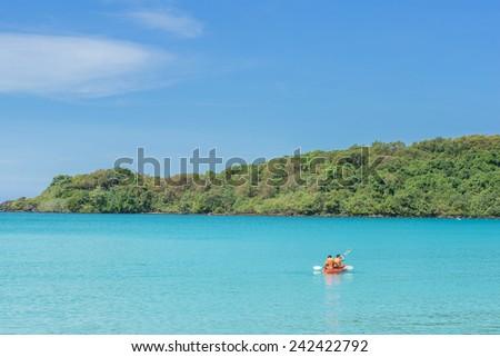 Tourist kayaking in the Thai ocean from backward view. Summer travel in Phuket ,Thailand. - stock photo