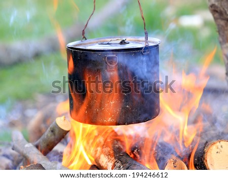 tourist kettle among hot flame of campfire - stock photo