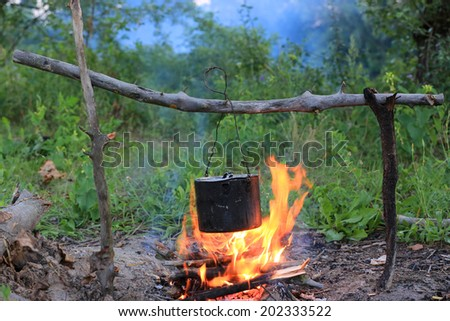 Tourist kettle on camp fire - stock photo
