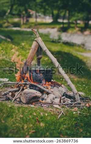 Tourist kettle on camp fire. Vintage colors. - stock photo