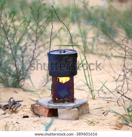 tourist kettle on portable heater - stock photo