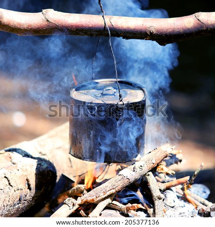 tourist kettle over campfire with blue smoke - stock photo