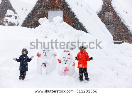 Tourist kids at historic Japanese village Shirakawa-go at winter, travel landmark of Japan - stock photo