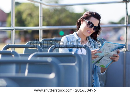tourist looking at map while on an open top bus touring the city - stock photo