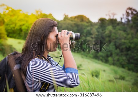 Tourist looking through binoculars considers wild birds in the Khao yai national park Thailand - stock photo