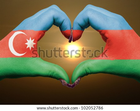 Tourist made gesture  by azerbaijan flag colored hands showing symbol of heart and love during sunrise - stock photo