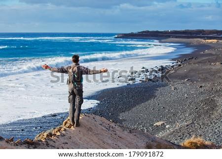 Tourist man looking to black beach. Lanzarote, Canary Islands, Spain. - stock photo