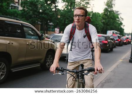 tourist man on a bike at city street - stock photo
